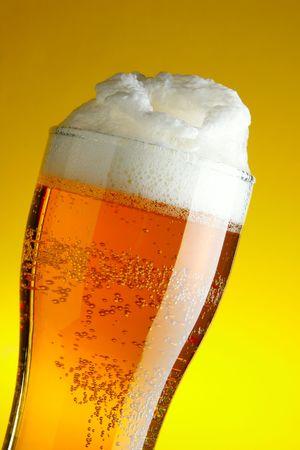 黄色の背景の上の泡のクローズ アップとビールのグラス