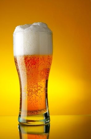 Glass of beer close-up with froth over yellow background Stock Photo - 2546459