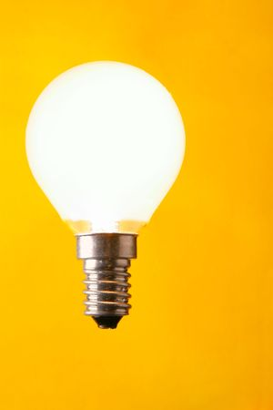 shining light: Shining light bulb close-up over yellow background