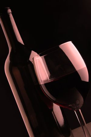 bocal: Still-life with wine bottle and footed glass over black background Stock Photo
