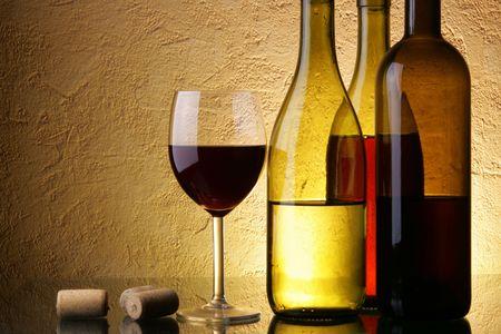 bouteille de vin: Nature morte avec trois bouteilles de vin et le verre textur� plus Banque d'images