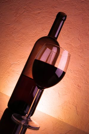 Still-life with glass of red wine and bottle over red textured background Stock Photo - 2570043