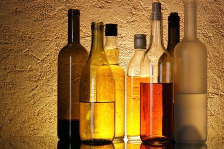 Bottles of alcoholic beverages over textured background photo