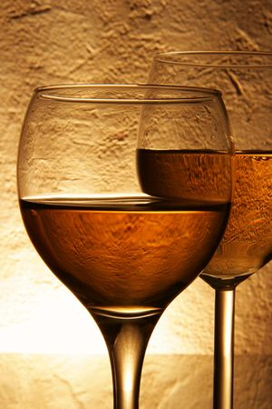 taster: Couple glasses with white wine over yellow background
