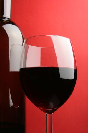 Glass and bottle of red wine over red background Stock Photo - 2847232
