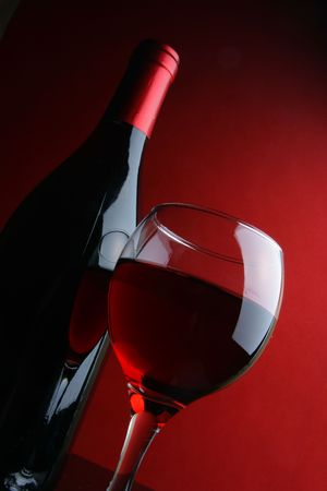 taster: Glass and bottle of red wine over dark red background