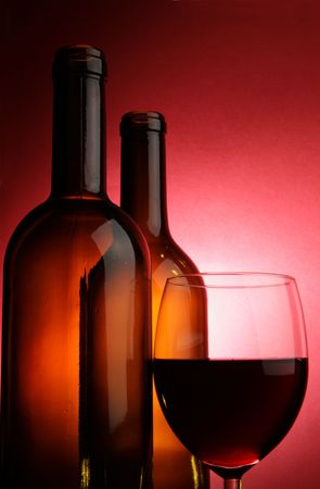 Glass of red wine and two bottles over deep red background photo