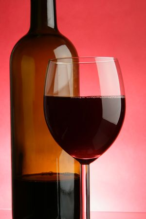 Glass and bottle of red wine over red background Stock Photo - 2900805