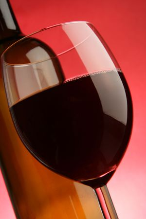 Glass and bottle of red wine close-up over red background Stock Photo - 2900804
