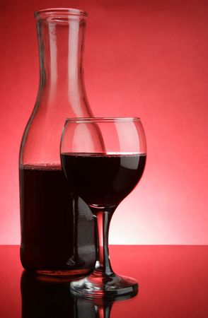Glass and jug of red wine over red background Stock Photo - 2900808