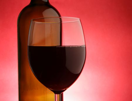 Glass and bottle of red wine over red background Stock Photo - 2924373