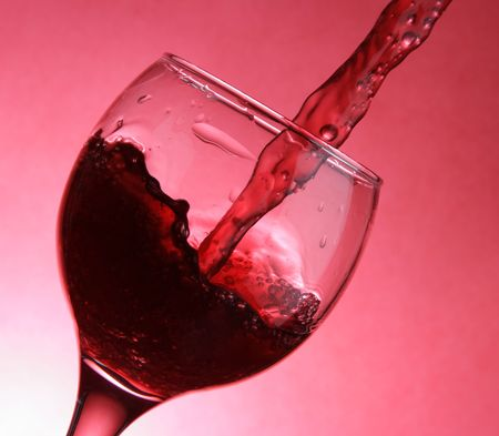 splutter: Closeup of pouring wine over red background Stock Photo