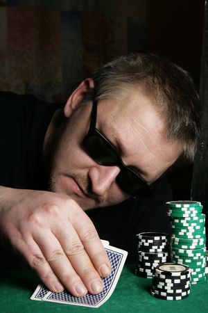 Poker gambler with sun glasses close-up. Focus on the hand and chips.