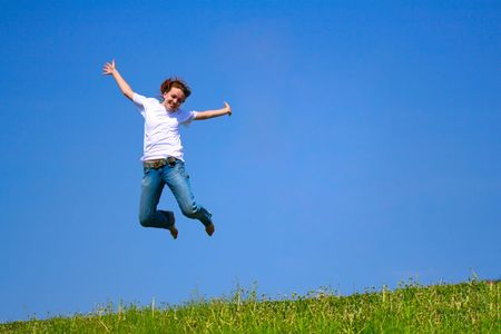 Young girl jumping against deep blue sky photo