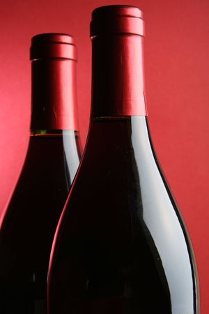 Two corked wine bottles closeup over red background photo