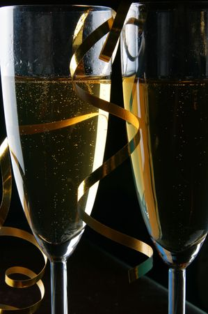 Two glasses of champagne and gold streamer over black background photo