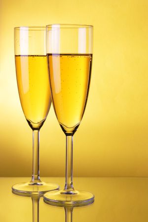 Couple glasses of champagne over yellow background photo