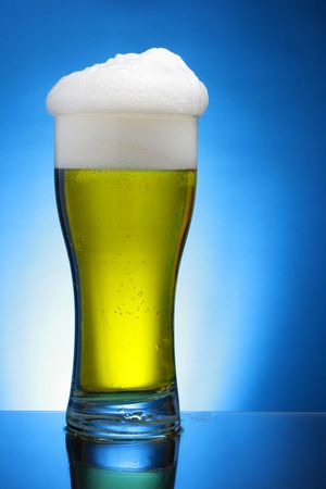 Glass of beer close-up with froth over blue background photo