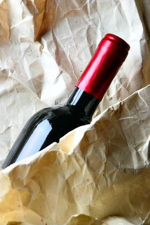 Bottle of red wine close-up and crumpled paper-bag photo