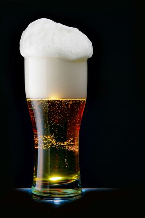 Glass of beer with froth over black background photo