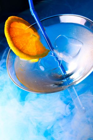 bar ware: Cocktail glass with orange slice and blue smoke in the background