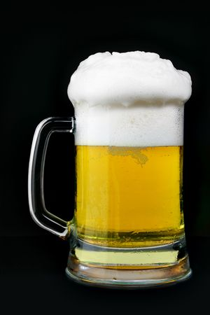 Mug of beer with froth over black background photo