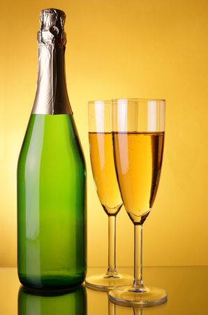 Bottle and glasses of champagne close-up over yellow background