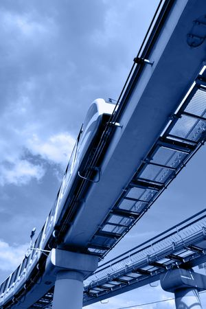 High speed monorail train on overpass toned in blue color photo