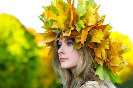 Beautiful blue-eyed woman with diadem made from yellow maple leaves photo