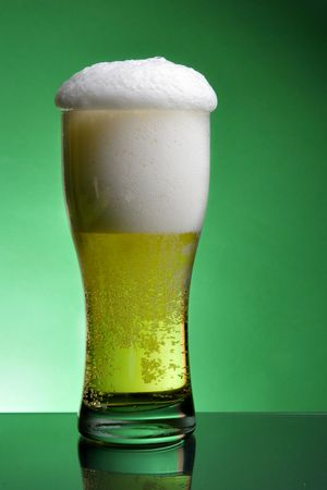 Glass of beer with froth over green background Stock Photo - 3314546