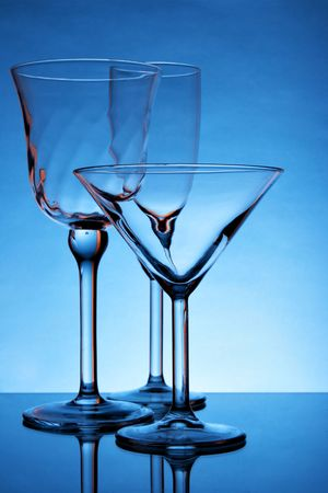 Still-life with empty glasses over blue background photo