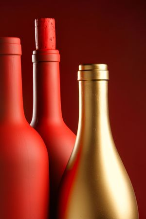 Two red and one gold bottle close-up photo