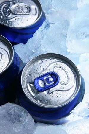 jarra de cerveza: Tres latas de aluminio de cerveza y el hielo cerca de Foto de archivo