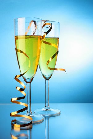 Two glasses of champagne with gold streamer over blue background