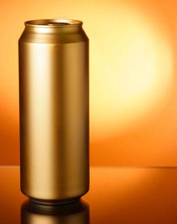 Golden beer can close-up over orange background photo