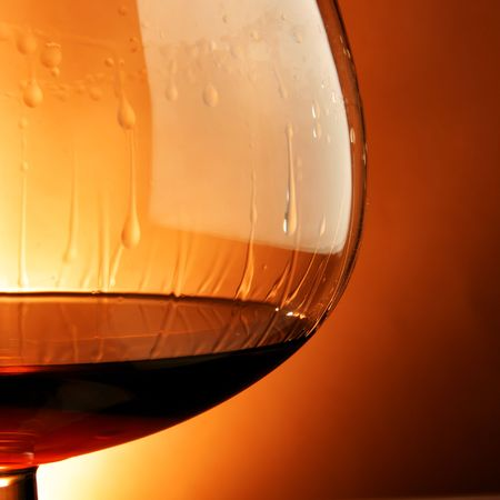 snifter: Snifter glass of cognac close-up over yellow background