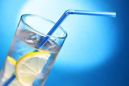 Drink with ice cubes and lemon slice close-up photo