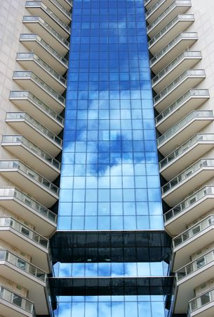 Perspective of tall modern building with sky reflection photo