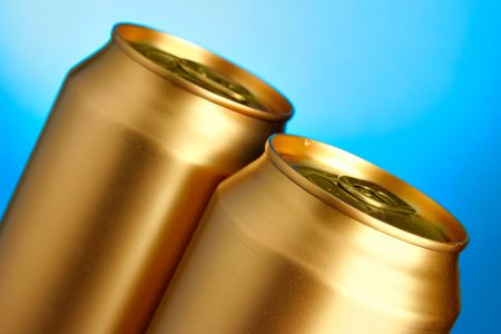 Golden beer cans close-up over blue background photo