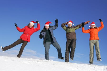 Friends with Santa hats dance on flank of hill photo