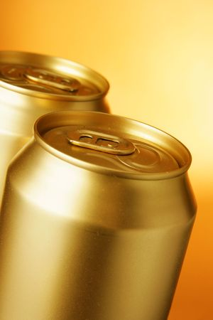 Golden beer cans close-up over yellow background photo