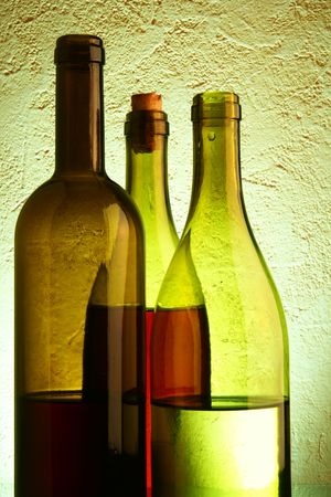 Still-life with three wine bottles over textured background photo