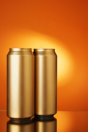 Two golden beer cans over orange  photo