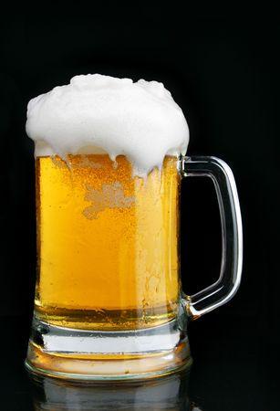 brew beer: Jarra de cerveza con espuma sobre fondo negro