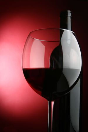 taster: Glass and bottle of wine over red background