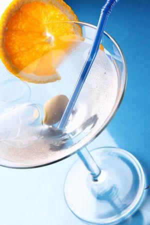 bar ware: Cocktail glass with orange slice over blue background