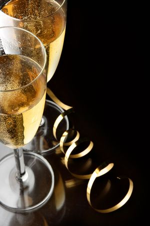 Couple glasses of champagne with gold streamer and space for your own text on right Stock Photo - 3829717