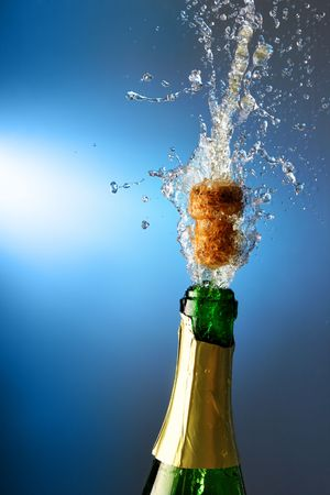 popping the cork: Bottle of champagne with splashes over blue background