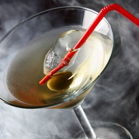 Cocktail glass with olive and smoke in the background photo