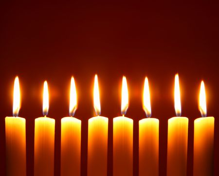 Eight alight candles close-up over red background photo